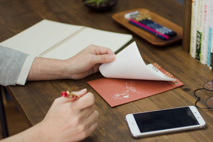 メモパットは、落ち着いたテクスチャの濃赤と濃青の紙に、用紙をめくると記のロゴマークが見えるデザイン